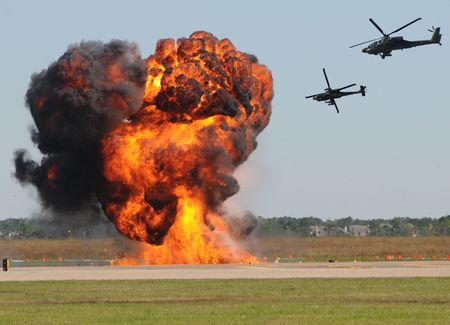 Two military helicopter attacking target on the ground