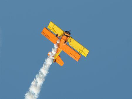 airborne vehicle: Old yellow biplane performing aerobatics