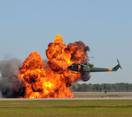 Helicopter hovering over giant explosion
