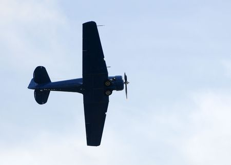Old propeller airplane in flight overhead photo