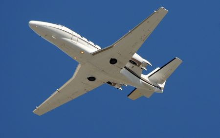 private jet: Modern private jet for charter travel passing overhead