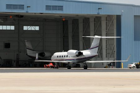 Business jet airplanes parked near airport hangar