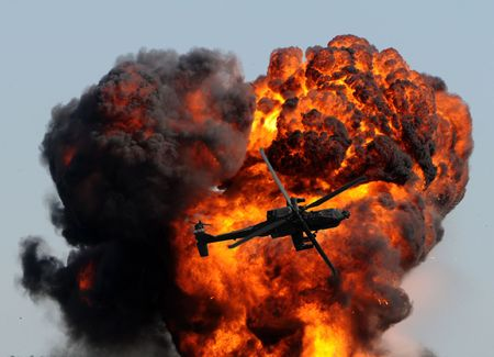 helicopter against giant fireball with smoke and flames Stock Photo
