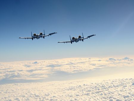 Two jetfighter in flight rear view above the clouds