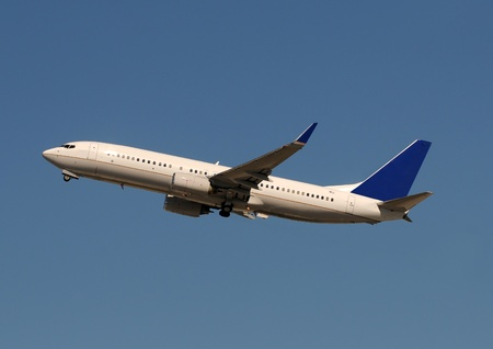 Passenger jet airplane taking off against blue sky