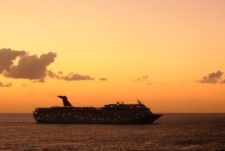 Cruise ship departing Caribbean port at sunset