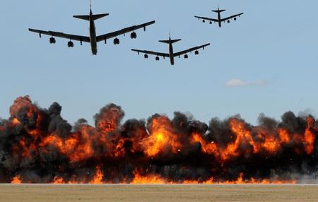 Zware bommenwerpers die bommen laten vallen met vuurballen en rook Stockfoto