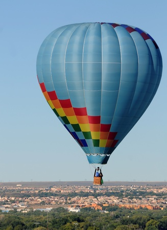 Colorful hot air balloon floating over countryside