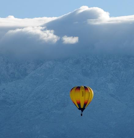 midair: Colorful hot air balloon in midair against snowy mountain
