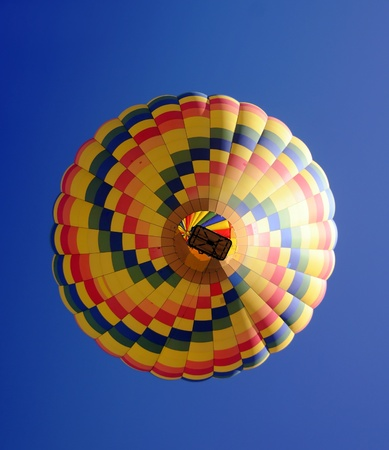 Colorful hot air balloon seen from below on blue sky