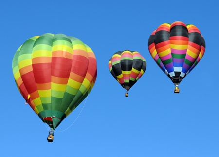Three colorful hot air balloons against blue sky