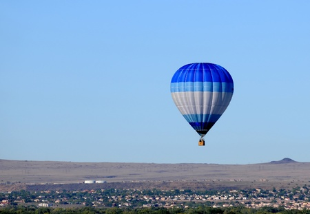 Blue hot air balloon floating over desert countryside