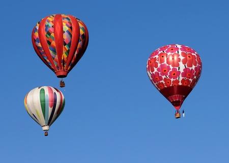 Drie kleurrijke luchtballon tegen de blauwe hemel Redactioneel