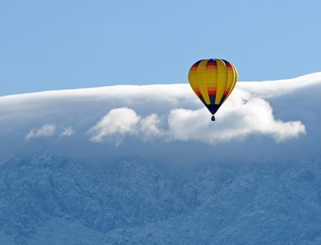 Yellow hot air balloon against a snowy mountain peak