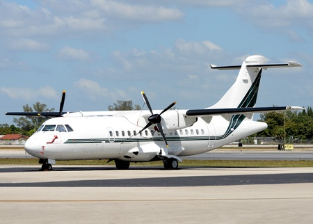 turboprop: White turboprop airplane parked on a tarmac Editorial