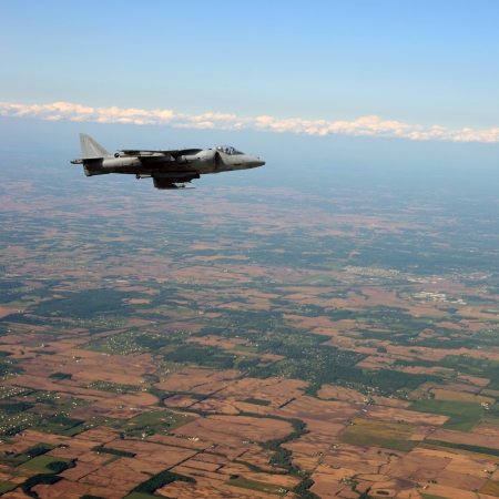 Jetfighter flying at high altitude above land photo