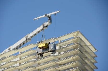 Workers clean and maintain exterior of highrise building Banco de Imagens