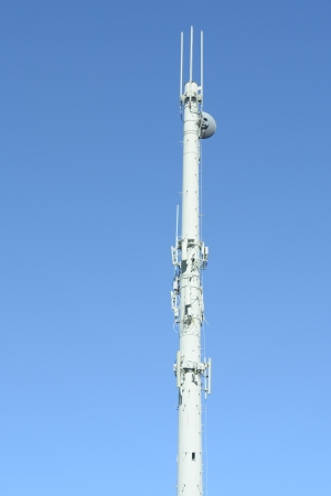 Modern communications antenna tower against blue sky