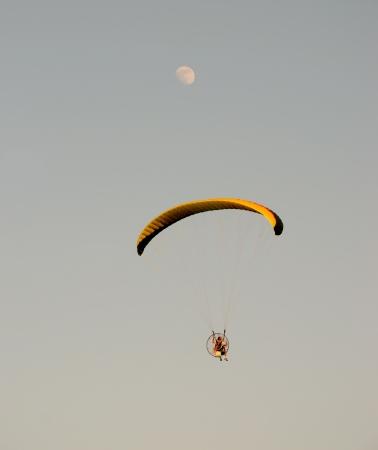 Motorized parachute flying in twilight