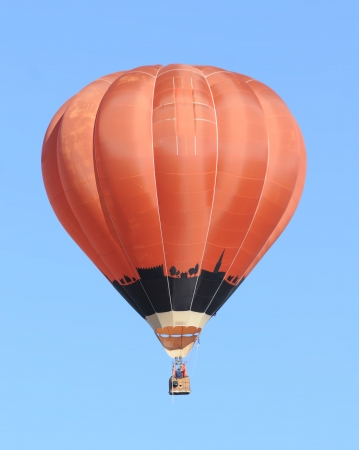 Bright red hot air balloon against blue sky photo