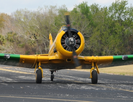 Yellow propeller airplane on the ground approaching  Editorial