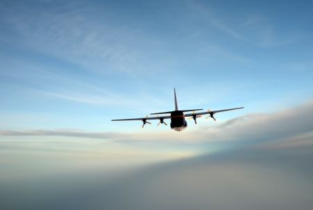 turboprop: Turboprop airplane flying at high altitude rear view