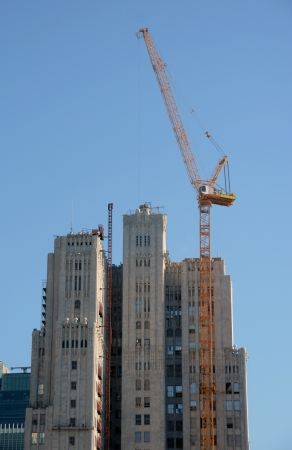 constructing: Tall crane constructing skyscraper