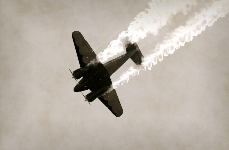 World War II era propeller airplane diving with a trail of smoke