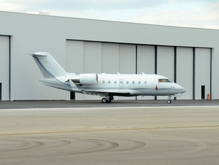 Modern corporate jet airplane in front of hangar