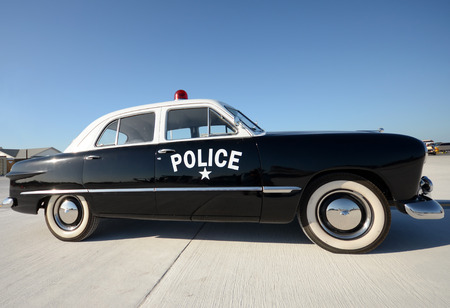 old people: Old American police car parked side view