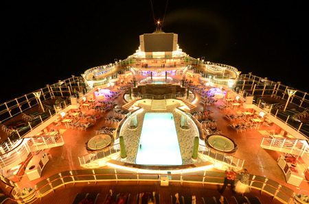 luxury liner: Cruise ship top deck under neon lights at night