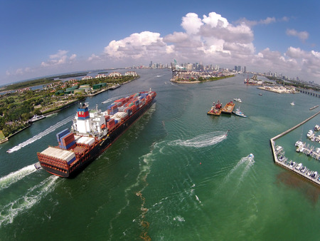 Heavy cargo ship enters the port of Miami aerial view Editorial