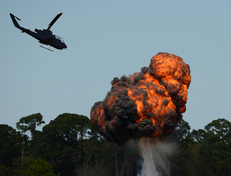 bombardment: Military helicopter flying over fiery explosion and fireball