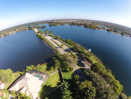 cutting through: Suburban road in Florida cutting through lakes aerial view