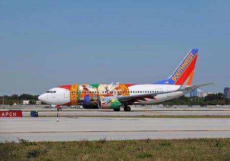 transporte terrestre: Fort Lauderdale, Florida - 19 de enero de 2011: Southwest Airlines Boeing 737-700 chorro de librea única llamada Florida Un rodaje en Fort Lauderdale Inernational aeropuerto. Suroeste tiene un número de aviones con temas bajo los destinos a los que sirve.