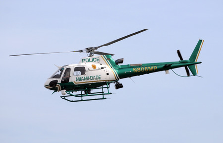 increasingly: Miami, Florida - December 26, 2009: Miami Dade County police helicopter departs on patrol. The county is increasingly using technology against crime fighting