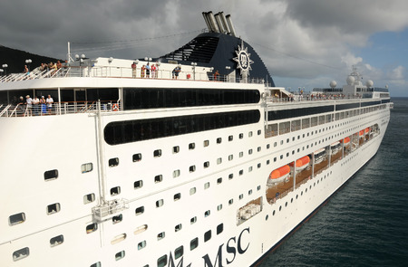 vacationers: Tortola, Caribbean - December 10, 2008: MSC Cruises ship leaving the Caribbean island of Tortola. The island is a popular stop for Caribbean cruise vacationers Editorial