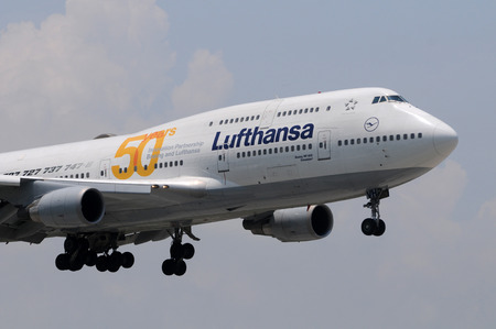 commemorating: Miami, USA - May 14, 2011: Lufthansa jumbo jet airplane landing at Miami AInternational Airport. The Boeing 747 jet beares special livery commemorating 50 years of cooperation between Lufthansa and Boeing