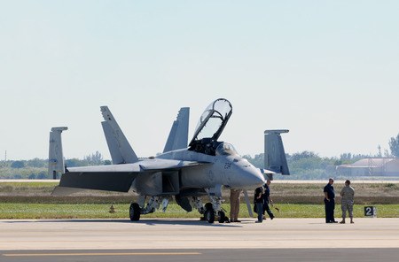 f 18: Miami, USA - Nov 6, 2010: Crews prepare a US Navy FA-18 fighter for flight at the Homestead Air Reserve base near Miami, Florida. The FA-18 is the most widely used carrier based fighter ofn the navy Editorial