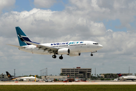 jetliner: Miami, USA - May 22, 2010: Westjet Boeing 737 passenger jet landing at Miami International Airport. Westject connects Canadian cities with many tourist destinations