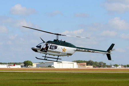 Lakeland, USA - April 1, 2012: Polk County, Florida Sheriff department helicopter Bell OH-58A departing on a patrol in early morning. Polk County is a rural area west of Orlando, Florida Editorial