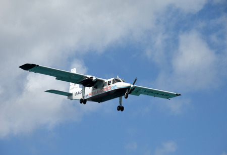 neighboring: PHILIPSBURG - DECEMBER 24: Anguilla Air Services turboprop airplane arrives in Philipsburg, Saint Maarten in the Caribbean. The airline connects the small island with neighboring airports.
