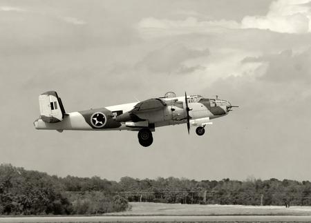 World War 2 era bomber in desert colors taking off