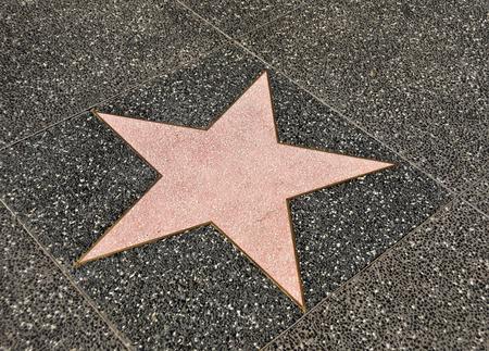 Blank walk of fame star on dark sidewalk
