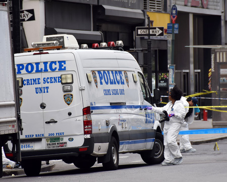 occurred: NEW YORK - MAY 13: NYPD Crime scene investigators probe the scene of a shooting in Midtown New York on May 13, 2015. The shooting occurred between police and a criminal fugitive.