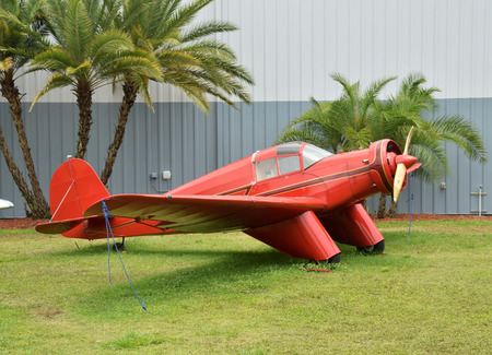 Retro red airplane in front of hangar