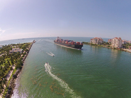 approaching: Cargo ship enters the Port of Miami seen from above