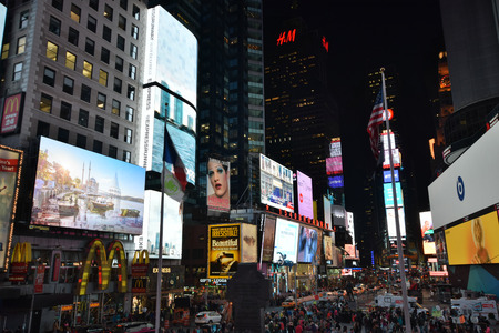 times square new york: New York, USA - April 28, 2015: Tourists gather at night on Times Square, New York under numerous billboards and neon on April 28, 2015