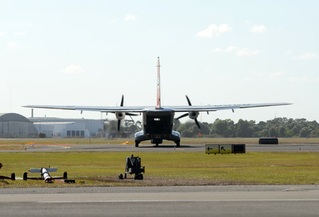 Coast Guard airplane departs on patrol seen from behind Stock Photo