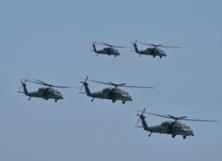 Team of five military helicopters on a mission